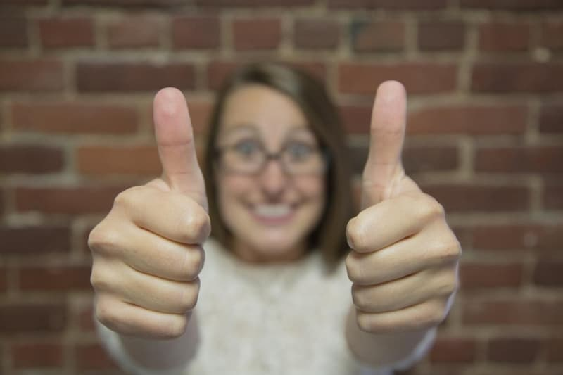 A girl with a  happy showing thumbs up  for anniversary gift coupons.