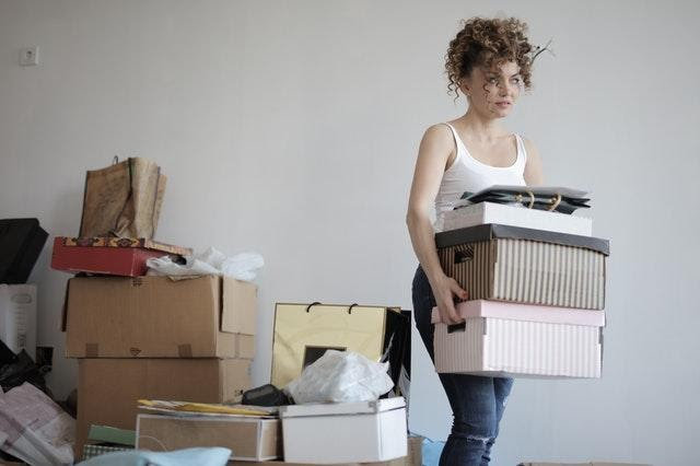 A woman choosing boxes when moving, a good thing to do when downsizing your home.